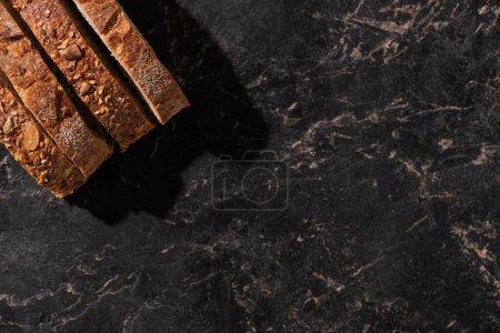 Photo pour Vue de dessus des tranches de pain frais sur la surface noire de pierre - image libre de droit