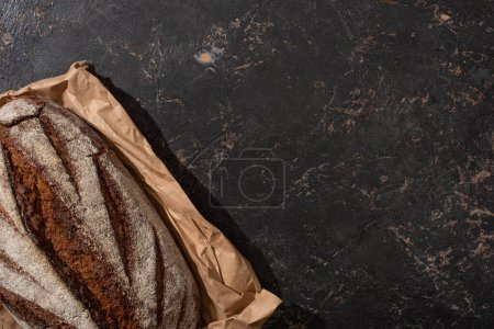 Photo pour Top view of organic brown bread loaf on paper on stone black surface - image libre de droit