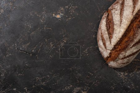 Photo for Top view of organic brown bread loaf on stone black surface - Royalty Free Image