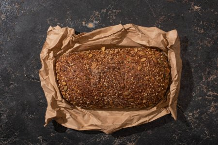 Photo for Top view of fresh baked loaf of whole grain bread in paper on stone black surface - Royalty Free Image