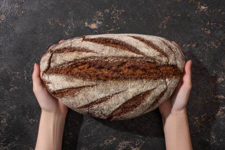 Photo pour Vue recadrée d'une femme tenant du pain brun sur une surface noire en pierre - image libre de droit