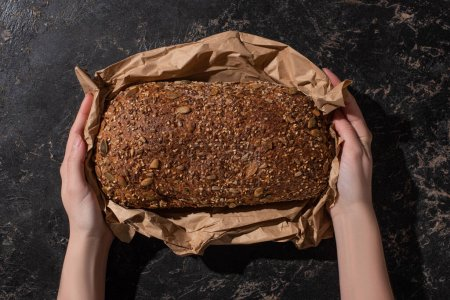 Photo for Cropped view of woman holding fresh baked loaf of whole grain bread in paper on stone black surface - Royalty Free Image