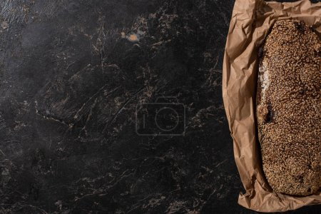 Photo for Top view of fresh baked loaf of whole grain bread with sesame in paper on stone black surface - Royalty Free Image