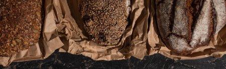 Draufsicht auf frisch gebackene Vollkornbrote in Papier auf steinschwarzer Oberfläche, Panoramaaufnahme