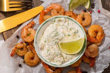 Photo pour Vue de dessus des crevettes frites sur papier parchemin avec sauce et lime près des couverts - image libre de droit