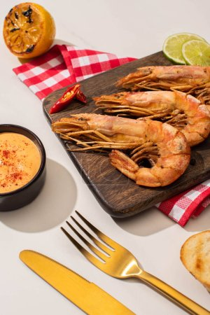 Photo for Fried shrimps on wooden board on plaid napkin with sauce and lime near golden cutlery on white background - Royalty Free Image