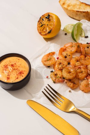 fried shrimps on parchment paper with sauce and lime near golden cutlery on white background