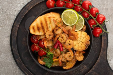 Photo for Top view of fried shrimps with grilled toasts, vegetables, cherry tomatoes and lime on wooden board on grey concrete background - Royalty Free Image