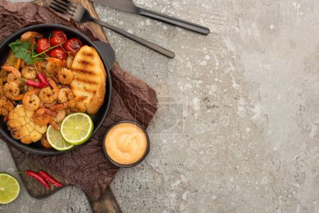 Photo for Top view of fried shrimps with grilled toasts, vegetables and lime served on board near cutlery and sauce on grey concrete background - Royalty Free Image
