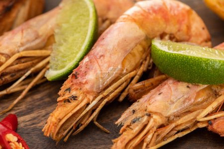 Photo for Close up view of fried shrimps with chili and lime on wooden board - Royalty Free Image