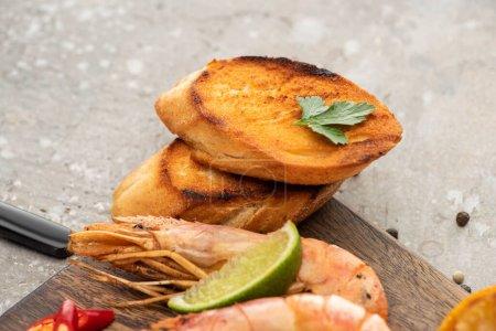 Photo pour Vue rapprochée des crevettes frites avec des toasts grillés et de la chaux sur planche de bois sur fond de béton gris - image libre de droit