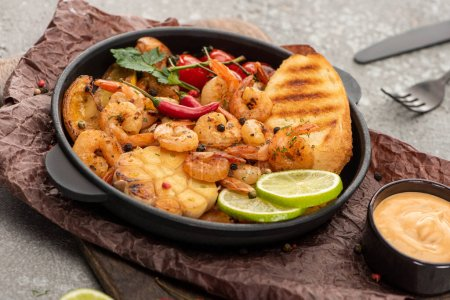 Photo for Selective focus of fried shrimps with grilled toasts, vegetables and lime on grey concrete background with cutlery - Royalty Free Image