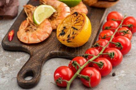 Photo pour Vue rapprochée des crevettes frites au citron et au citron vert près des tomates cerises sur planche de bois sur fond de béton gris - image libre de droit