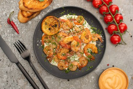 Photo for Top view of fried shrimps in sauce with dill and lemon near cutlery, cherry tomatoes and toasts on grey concrete background - Royalty Free Image