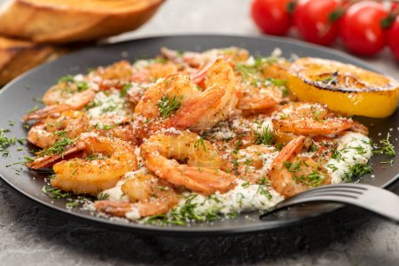 Photo for Selective focus of fried shrimps in sauce with dill and lemon in black plate on grey concrete background - Royalty Free Image
