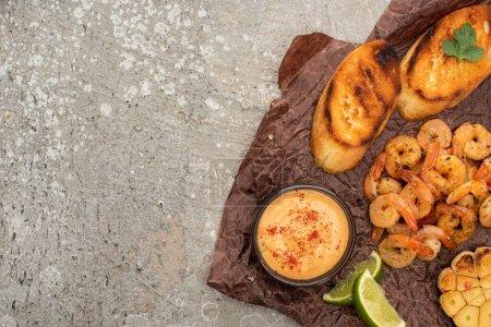 Photo pour Vue du dessus des crevettes frites avec sauce, toasts grillés, chaux sur papier parchemin sur fond de béton gris - image libre de droit