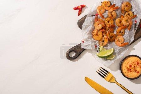 Photo pour Vue du dessus des crevettes frites sur papier sulfurisé sur carton avec couverts, piment, sauce et citron vert sur fond blanc - image libre de droit