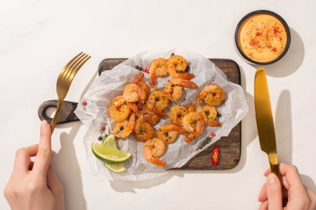 Photo for Cropped view of woman eating fried shrimps on parchment paper on wooden board with chili pepper, sauce and lime on white background - Royalty Free Image