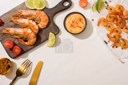 Photo for Top view of fried shrimps on parchment paper and wooden board near grilled lemon, sauce and cutlery on white background - Royalty Free Image