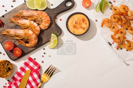 Photo for Top view of fried shrimps on parchment paper and wooden board with cutlery, plaid napkin, vegetables, sauce and lime on white background - Royalty Free Image