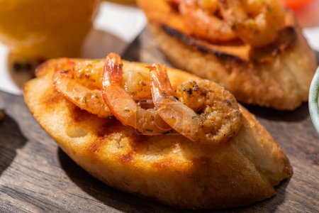 Photo for Close up view of canape with toast bread and fried shrimps on wooden board - Royalty Free Image
