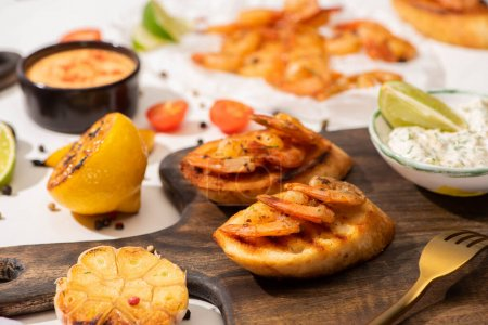 Photo for Selective focus of canape with fried shrimps with sauce on wooden board - Royalty Free Image