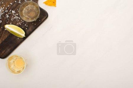 Foto de Vista superior de tequila dorado con cal, sal sobre tabla de cortar de madera sobre superficie de mármol blanco - Imagen libre de derechos