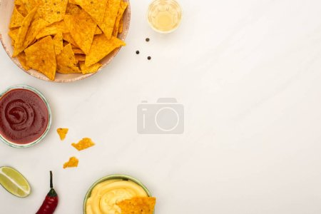 Photo for Top view of tequila with lime, chili pepper, sauces and nachos on white marble surface - Royalty Free Image