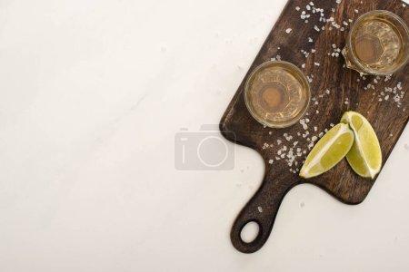 Foto de Vista superior del tequila dorado con cal, sal en tabla de corte de madera sobre superficie de mármol blanco. - Imagen libre de derechos