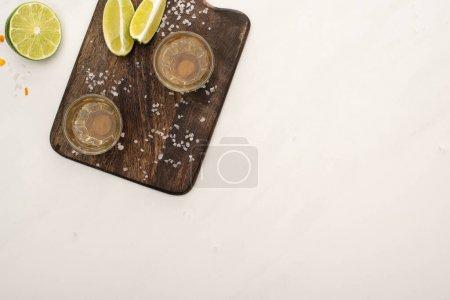 Photo pour Vue de dessus de tequila dorée à la chaux, sel sur planche à découper en bois sur marbre blanc - image libre de droit