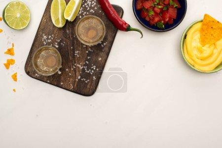 Blick von oben auf goldenen Tequila mit Limette, Chilipfeffer, Salz und Nachos mit Käsesauce in der Nähe des Holzschneidebretts auf weißem Marmor