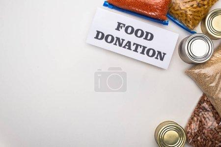 Photo pour Vue du haut des boîtes de conserve et des gruaux dans des sacs à fermeture à glissière près de la carte avec lettrage de don d'aliments sur fond blanc - image libre de droit