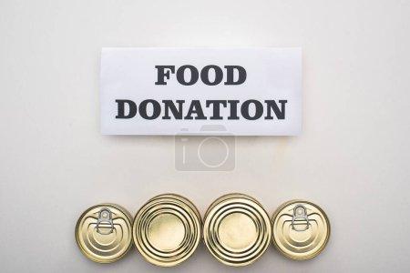 Photo pour Vue du dessus des canettes avec de la nourriture en conserve sur fond blanc avec carte de don alimentaire - image libre de droit