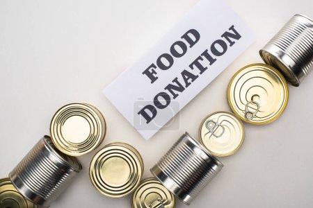 Photo pour Vue du haut des boîtes de conserve de nourriture en conserve sur fond blanc avec carte de don de nourriture - image libre de droit