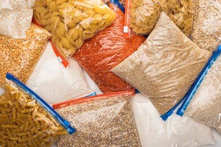Photo pour Vue du dessus des gruaux et des pâtes dans des sacs à fermeture éclair, concept de don alimentaire - image libre de droit