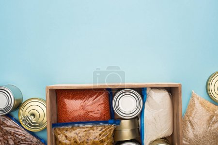 Photo for Top view of cans and groats in zipper bags in wooden box on blue background, food donation concept - Royalty Free Image