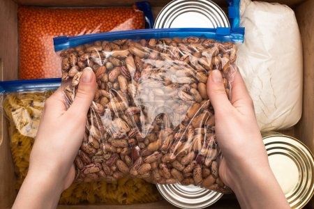 Photo for Cropped view of woman holding  beans in zipper bag, food donation concept - Royalty Free Image