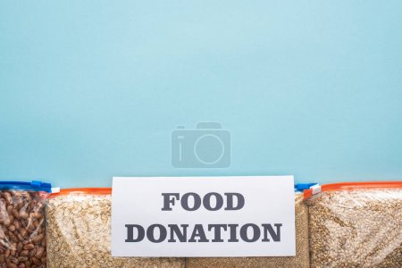 Photo for Top view of groats in zipper bags near card with food donation lettering on blue background - Royalty Free Image
