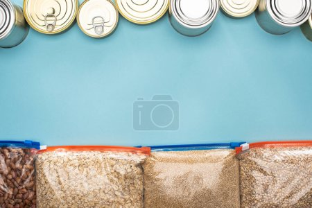 top view of cans and groats in zipper bags on blue background with copy space