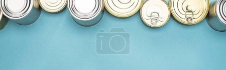 Photo pour Vue du haut des boîtes de conserve sur fond bleu avec espace de reproduction, concept de don de nourriture - image libre de droit