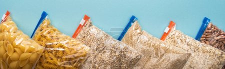 Photo for Top view of pasta, beans and groats in zipper bags on blue background, food donation concept - Royalty Free Image