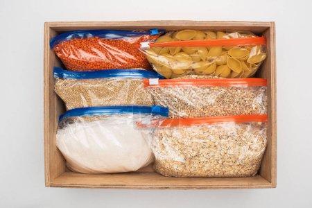 Photo pour Vue du dessus des pâtes et des gruaux dans des sacs à fermeture éclair dans une boîte en bois sur fond blanc, concept de don alimentaire - image libre de droit
