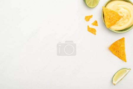 Photo for Top view of corn nachos with lime and cheese sauce on white background - Royalty Free Image