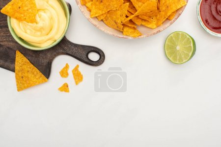 Photo for Top view of corn nachos with lime, ketchup, cheese sauce on wooden cutting board on white background - Royalty Free Image