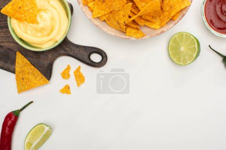 Photo for Top view of corn nachos with chili pepper, lime, ketchup, cheese sauce on wooden cutting board on white background - Royalty Free Image