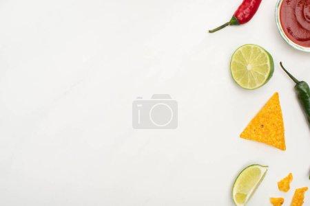 Photo pour Vue du dessus des nachos de maïs au citron vert, piments, ketchup sur fond blanc - image libre de droit