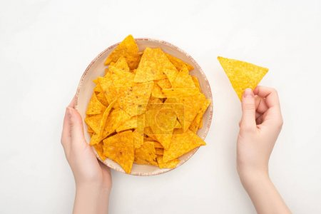 Photo for Cropped view of woman holding bowl of corn nachos with on white background - Royalty Free Image