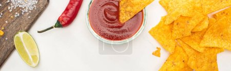 Photo for Top view of corn nachos with lime, chili, ketchup on white background, panoramic shot - Royalty Free Image