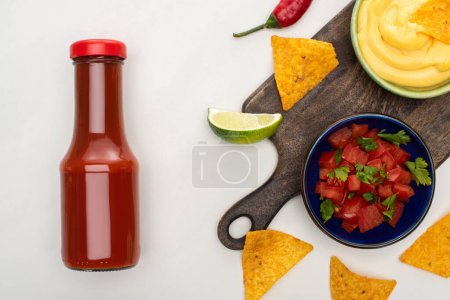 Photo for Top view of corn nachos with lime, chili, ketchup and cheese sauce on wooden cutting board on white background - Royalty Free Image