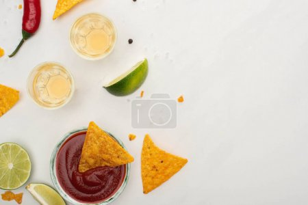 Photo for Top view of corn nachos with lime, chili, ketchup and tequila on white background - Royalty Free Image